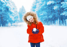 Cheerful positive child with snowball having fun outdoors Royalty Free Stock Images