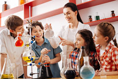 Cheerful positive children being involved in the lesson. Interesting lesson. Cheerful positive cute children standing around the teacher and being involved in stock photos