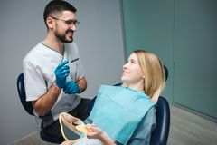Cheerful positive dentist and client in dentistry. They look at each other and smile. Female client sit in chair and. Hold mirror. She look satisfied stock images