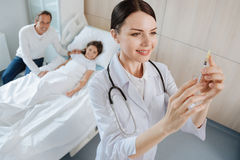 Cheerful positive doctor preparing for an injection Stock Photos
