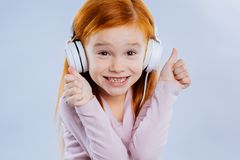 Cheerful positive girl enjoying listening to music stock image
