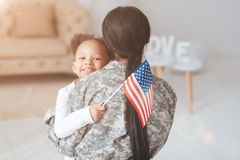 Cheerful positive girl holding an American flag. Patriot of the country. Cheerful positive cute girl hugging her mother and smiling while holding an American stock image