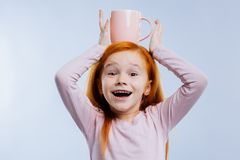 Cheerful positive girl standing with a cup on the head stock photography