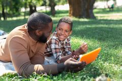Cheerful positive man showing a picture to his son. New technology. Cheerful positive men showing a picture to his son while lying with him on the grass stock photo