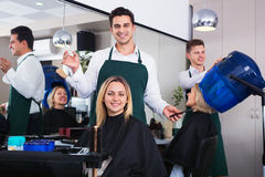 Cheerful positive pman cutting long hair of girl Royalty Free Stock Photos