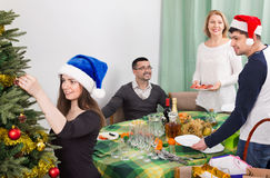 Cheerful positive smiling family setting table for dinner. And decorating Christmas tree Stock Photos