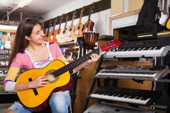 Cheerful positive  teenage girl posing with classical guitar Stock Photography
