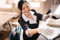 Cheerful positive woman cleaning the hotel room. My job. Cheerful positive nice woman holding a duster and using various cleansing agents while cleaning the Royalty Free Stock Photos