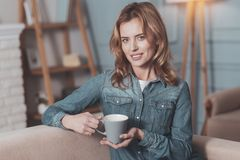 Cheerful positive woman holding a cup of tea royalty free stock photography