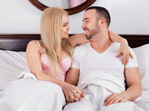 Cheerful positive young couple posing in family bed Stock Image