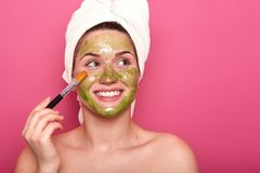 Cheerful positive young female putting colorful mask on her face with help of professional brush, looking aside, being happy. Attractive girl enjoys spending royalty free stock image