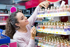 Cheerful positive young  woman choosing fragrance Royalty Free Stock Images