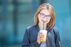 Cheerful pre-teenage girl drinking juice. Girl with dental teeth braces and glasses Stock Image