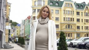 Cheerful pregnant female smiling, posing at camera, walking along city centre stock photography