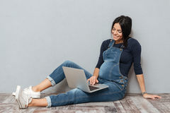 Cheerful pregnant lady sitting on floor using laptop computer. Stock Image