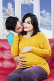 Cheerful pregnant mother kissed by her husband Stock Image
