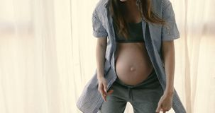 Cheerful pregnant woman dancing. Crop faceless view excited pregnant woman in expectancy wearing top and dancing emotionally having fun at home alone stock footage