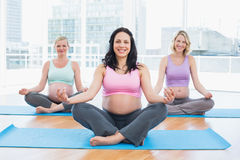 Cheerful pregnant women in yoga class sitting on mats Stock Photo
