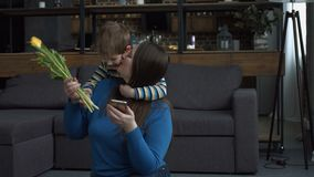 Joyful little son giving flowers to his mother. Cheerful preschool boy giving yellow tulips flowers to his happy mother , emabracing her from behind and kissing