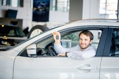 Young cheerful man showing key in his car in dealership royalty free stock photos