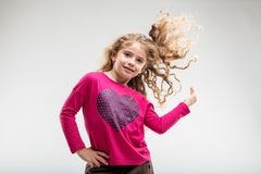 Cheerful preteen girl playing with her curly hair. Smiling schoolgirl playing with her curly hair against plain background Stock Photo