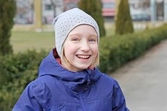 Cheerful preteen girl 9-11 year old laughing on a walk outdoors. royalty free stock photography