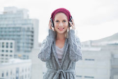 Cheerful pretty blonde listening to music outdoors Stock Photos