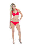 Cheerful pretty blonde model posing with hand on hips wearing red bikini Royalty Free Stock Images
