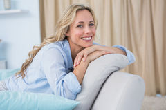 Cheerful pretty blonde sitting on couch Stock Photography