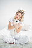 Cheerful pretty blonde wearing hair curlers holding teddy bear Stock Images