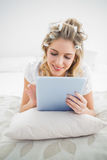 Cheerful pretty blonde wearing hair curlers scrolling on tablet Royalty Free Stock Photo
