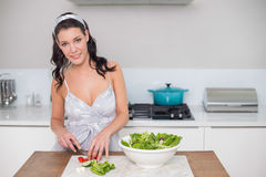 Cheerful pretty brunette chopping vegetables Stock Photo