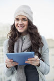 Cheerful pretty brunette holding her tablet computer Royalty Free Stock Image