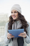 Cheerful pretty brunette holding her tablet Royalty Free Stock Photography