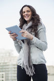 Cheerful pretty brunette holding her tablet pc Stock Photo