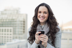 Cheerful pretty brunette sending a text on her smartphone Royalty Free Stock Image