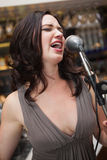 Cheerful pretty brunette singing with her microphone Royalty Free Stock Photos