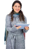 Cheerful pretty brunette wearing winter clothes holding her tablet Stock Photos