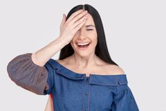 Cheerful pretty charming woman in jeans dress with dark hair smiling happily, having fun indoors, closing one eye with hand. royalty free stock photography