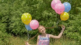 Cheerful and pretty girl with colorful balls attached to her hair and braids on her head. Funny idea with balloons. royalty free stock photo