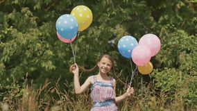 Cheerful and pretty girl with colorful balls attached to her hair and braids on her head. Funny idea with balloons. Cheerful and pretty girl with colorful balls stock video footage