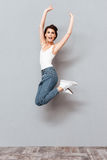 Cheerful pretty girl jumping over gray background Stock Images