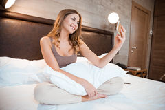 Cheerful pretty girl sitting on bed using cellphone Royalty Free Stock Images