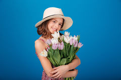 Cheerful pretty little girl in hat holding bouquet of flowers Stock Photos