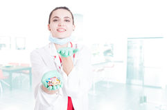 Cheerful pretty medic offering you capsules. As illness cure concept with text area Stock Images