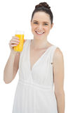 Cheerful pretty model in white dress holding glass of orange juice Stock Photography