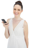 Cheerful pretty model in white dress sending text message Royalty Free Stock Photo