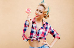 Cheerful pretty pinup girl eating sweet lollipop Stock Photography