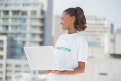 Cheerful pretty volunteer holding laptop Royalty Free Stock Image