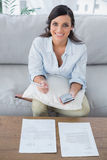 Cheerful pretty woman doing her accounts Stock Image